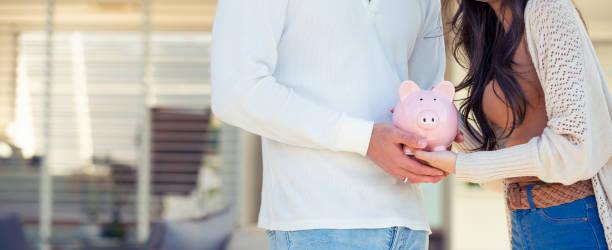 Paar hält ein Sparschwein in ihrer neuen Heimat. Bausparen-Konzept. – Foto