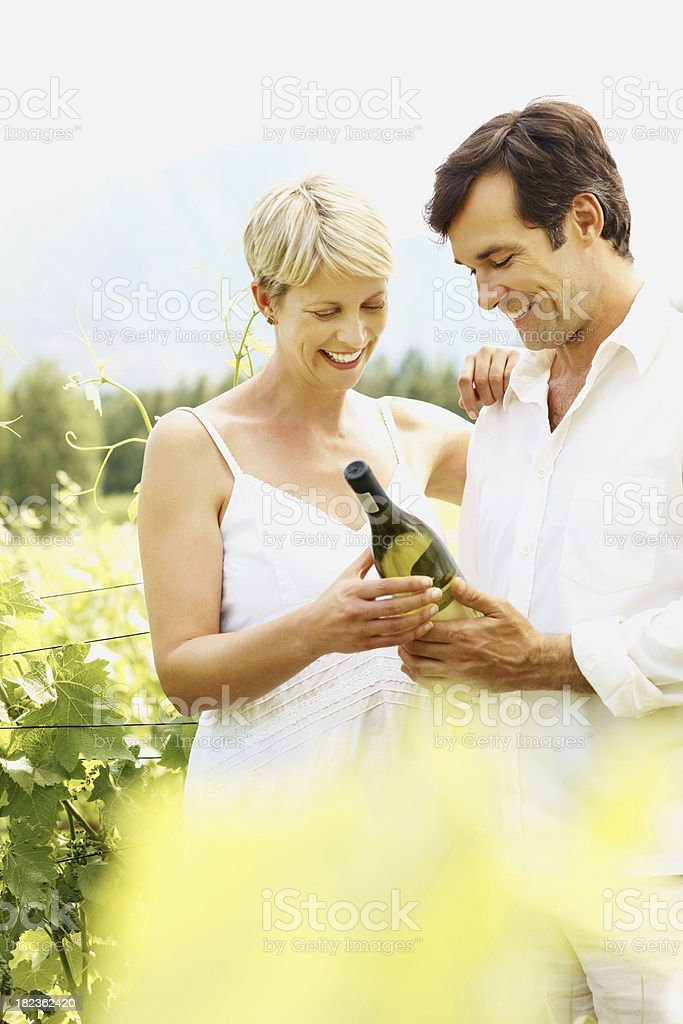Couple holding a wine bottle in vineyard royalty-free stock photo
