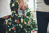Man and woman, married couple relaxing together at home, standing next to Christmas day. holding baby shoes.