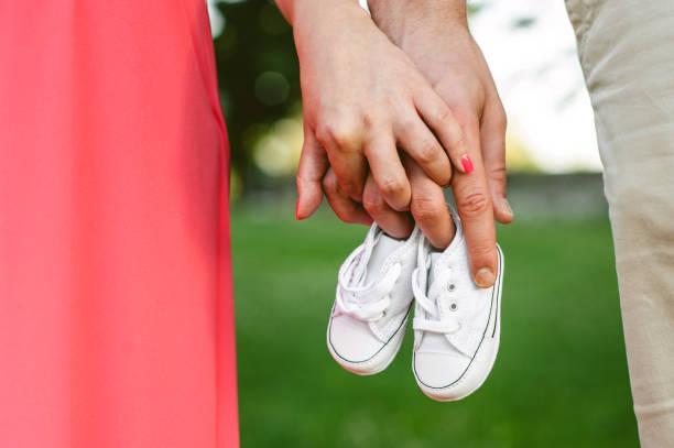 Couple Holding Baby Shoes stock photo