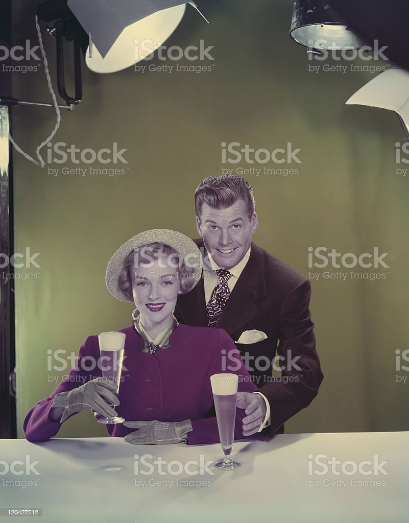 Couple holding beer glasses, smiling, portrait stock photo