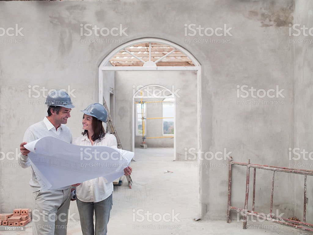 Coppia holding cianografie in casa in costruzione - foto stock