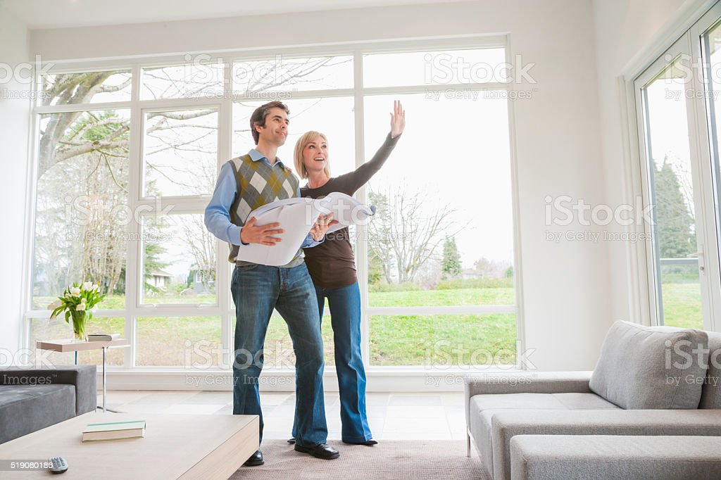 Couple holding building plans and discussing remodel stock photo