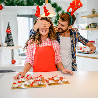 Box with tasty Christmas cookies, gingerbread on in man and woman hands. holiday, celebration and cooking concept.