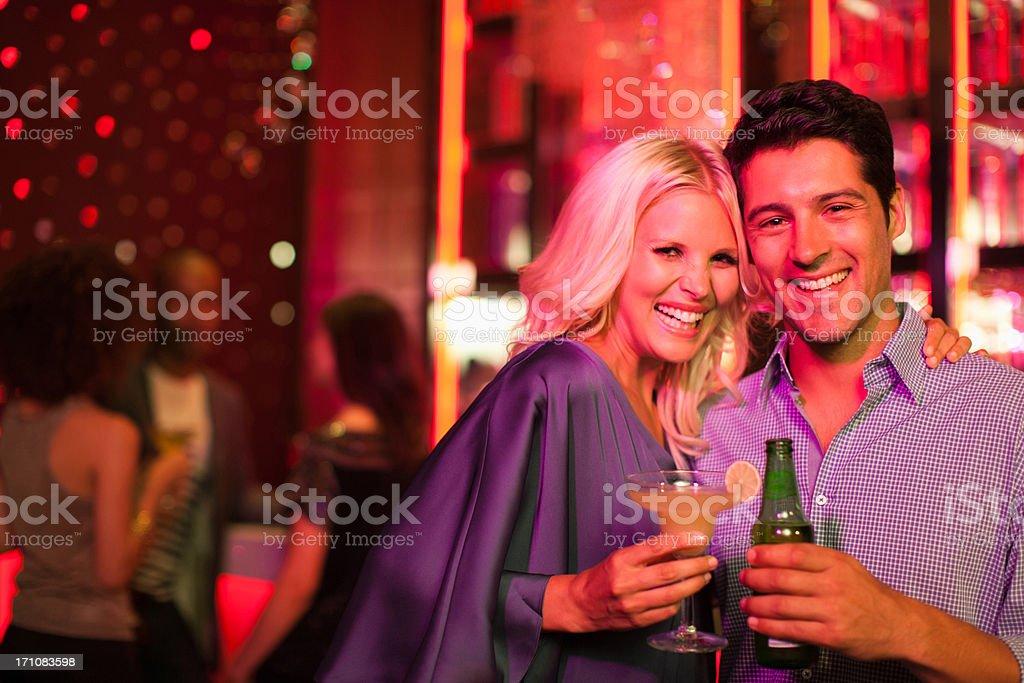 Couple holding drinks in nightclub stock photo