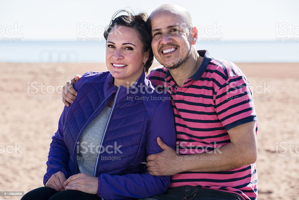 couple holding each other on the beach stock photo