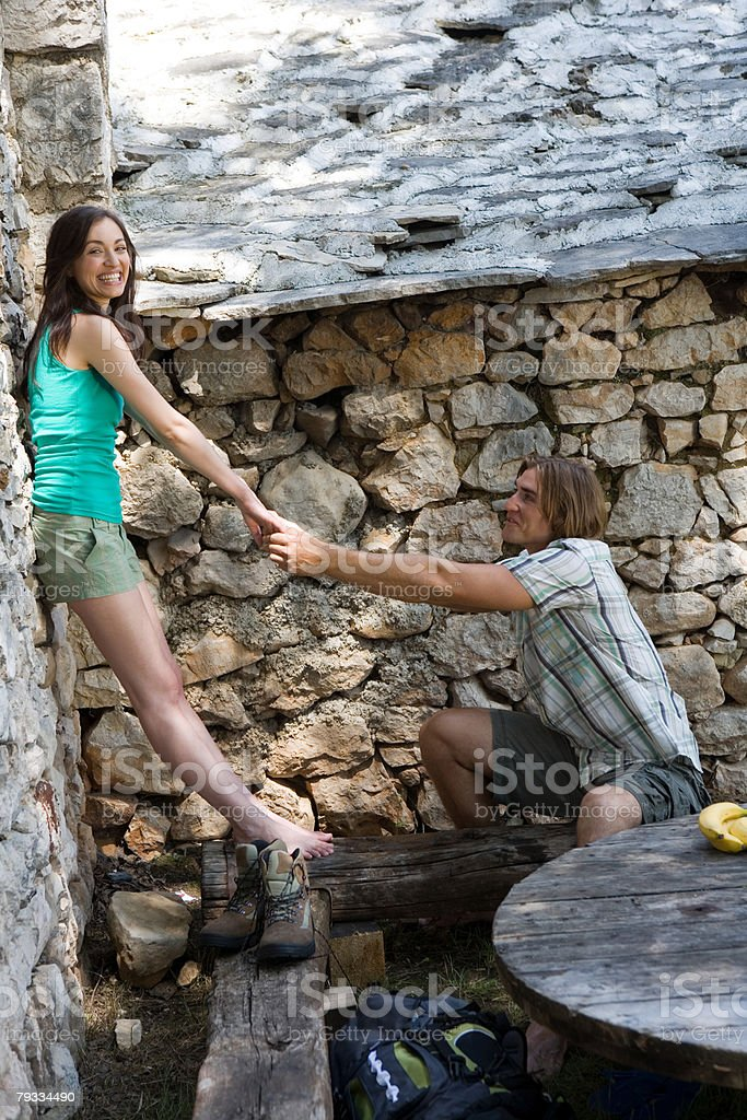 Couple holding hands against stone wall royalty-free stock photo
