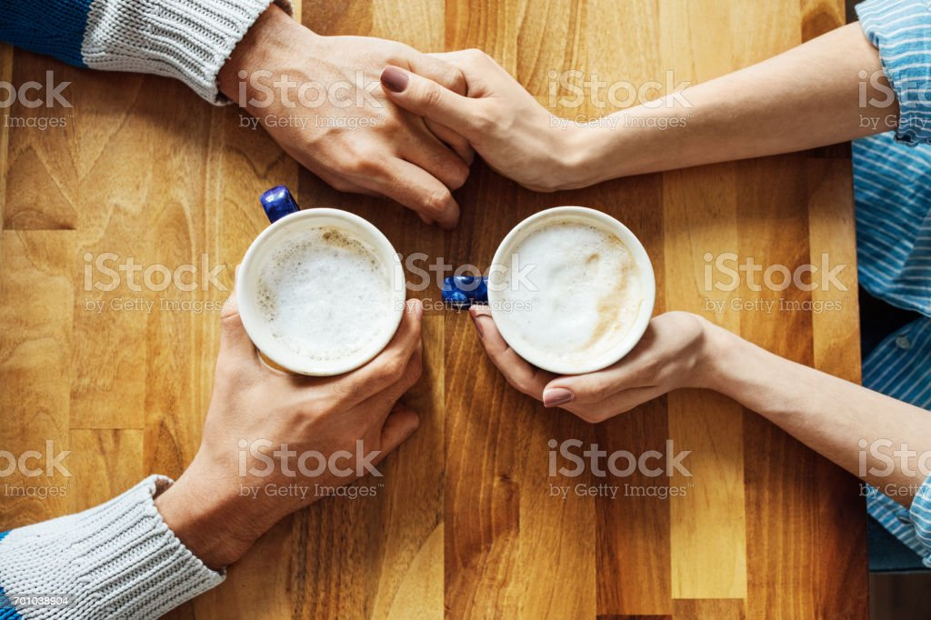 Couple holding hands and coffee cups at cafe table stock photo