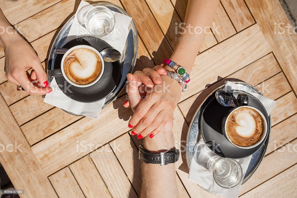 Couple holding hands and drinking coffee in cafe stock photo