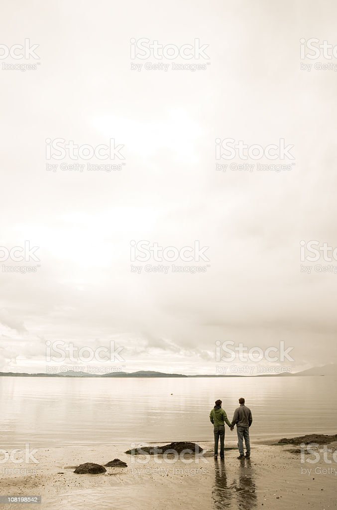 Couple Holding Hands and Looking Out at Water stock photo