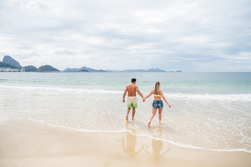 Couple holding hands and paddling in sea