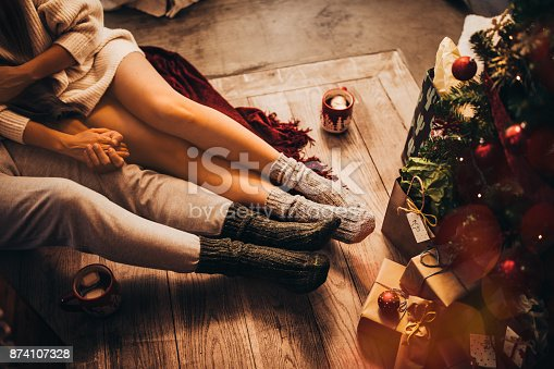 Romantic couple cozy at home with hot chocolate sitting under Christmas tree on Christmas eve