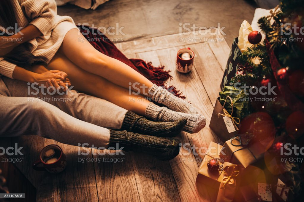Couple holding hands and relaxing sitting under Christmas tree stock photo