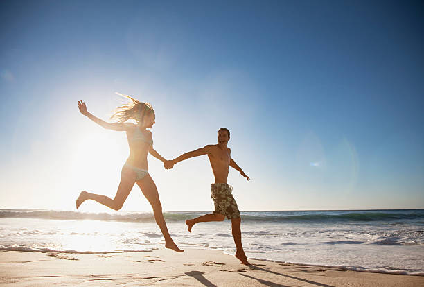 Couple holding hands and running on beach stock photo