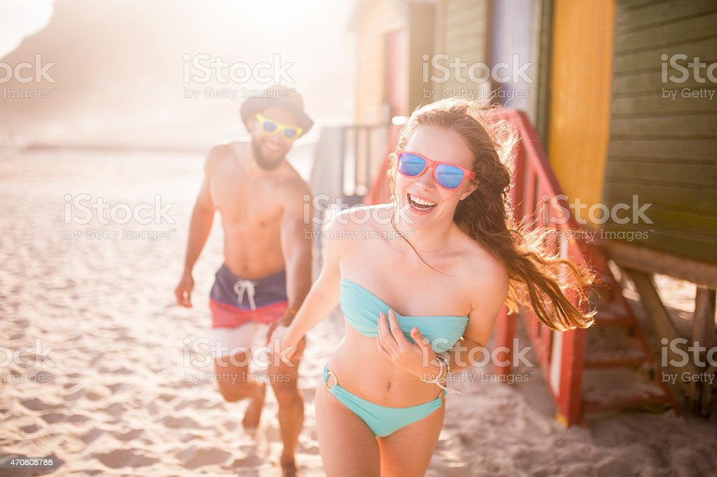 Couple holding hands and running past beach huts stock photo