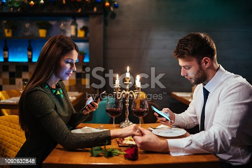 Couple holding hands and texting on the smart phone