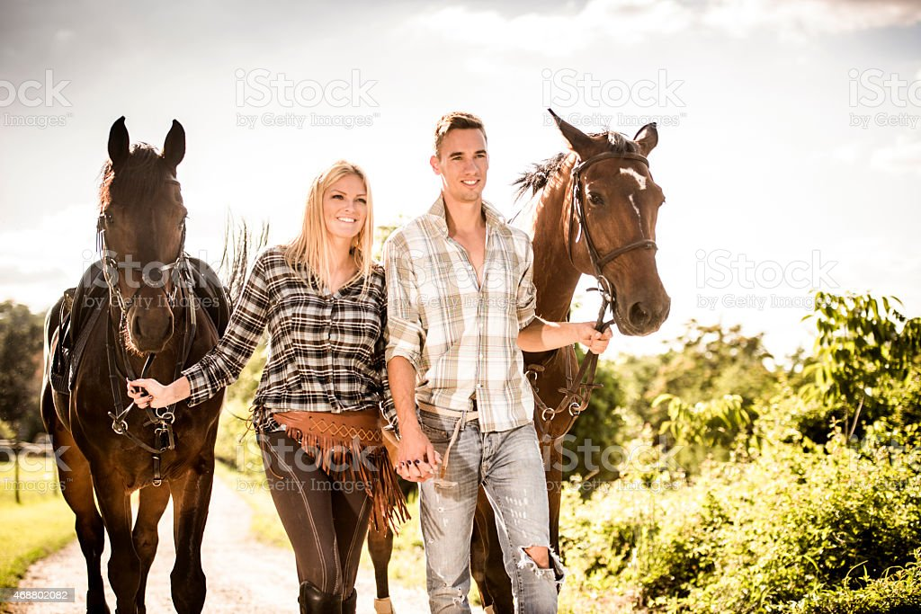 Couple Holding Hands And Walking Their Horses Stock Photo Download Image Now Istock