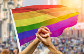 Cropped shot of a couple holding hands and wave in front of a rainbow flag flying on the sidelines of a summer gay pride parade