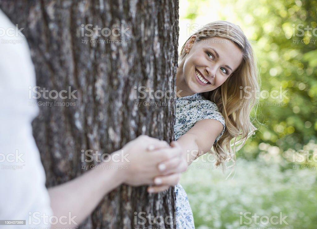 Couple holding hands around tree royalty-free stock photo