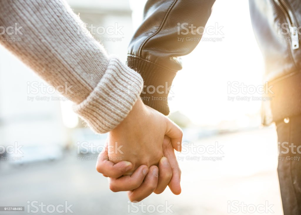 couple holding hands at arch du triomphe stock photo