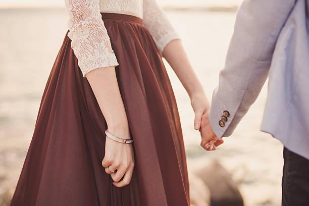 paar hände halten am sonnenaufgang - verlobungskleider stock-fotos und bilder