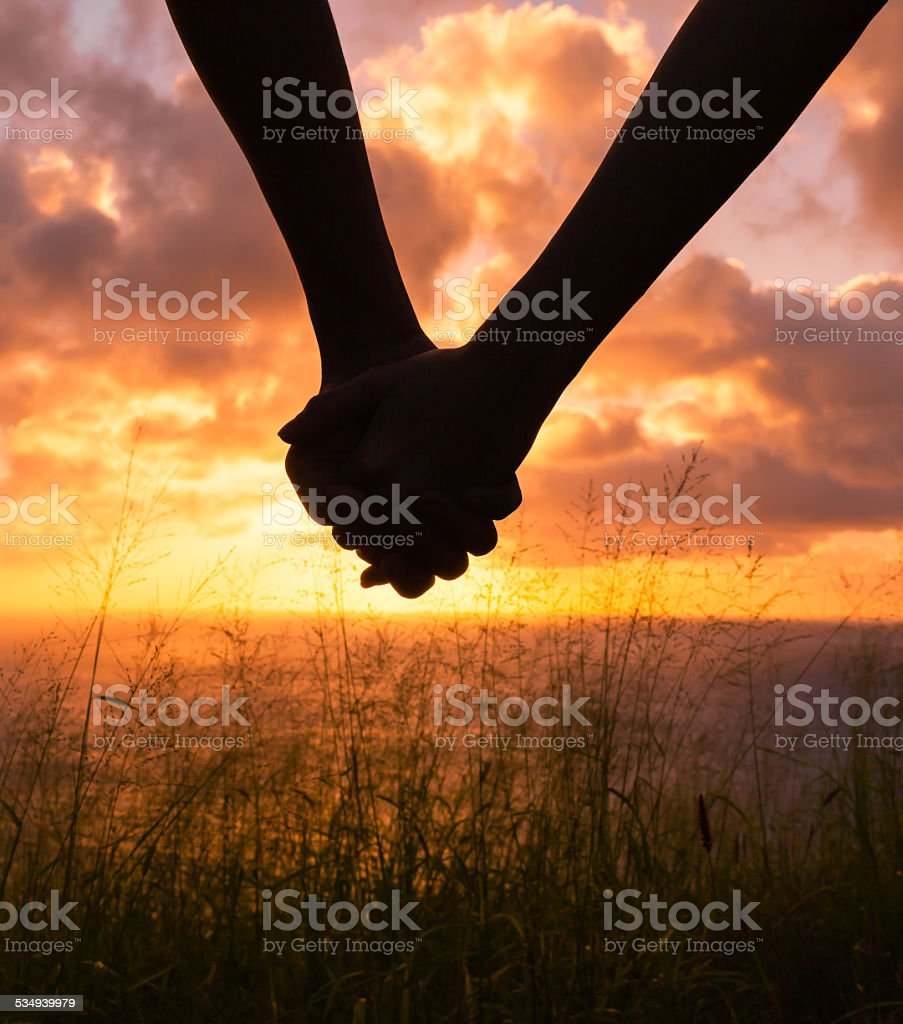 Couple Holding Hands At Sunset Stock Photo