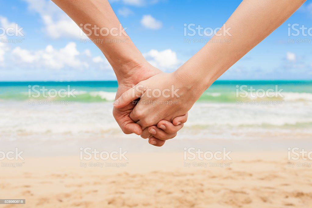Couple holding hands at the beach stock photo