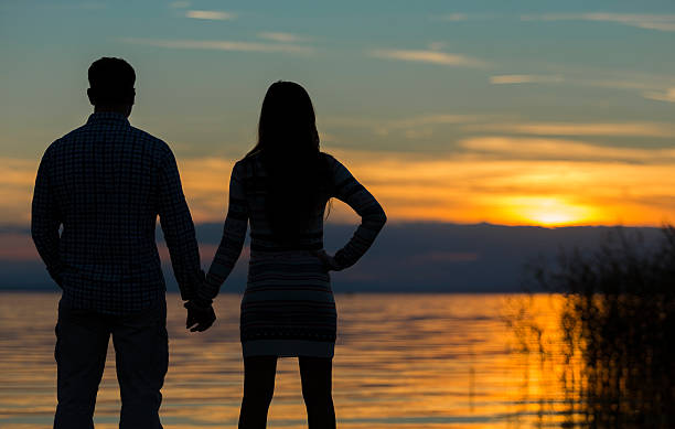 couple holding hands at the lake stock photo