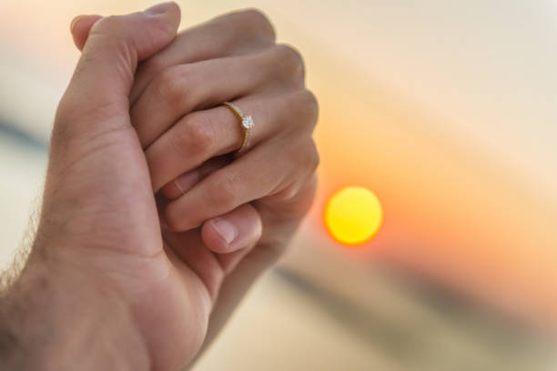 couple holding hands during sunset - diamond ring hand stock photos and pictures
