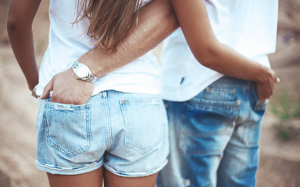 Couple holding hands in each other pocket stock photo
