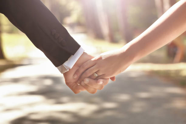 couple holding hands in front of a sunset - diamond ring hand stock photos and pictures