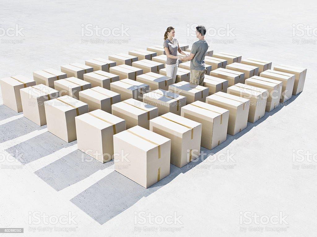 Couple holding hands in line of boxes royaltyfri bildbanksbilder