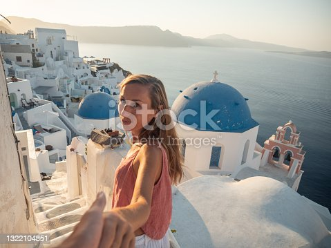 istock Couple holding hands in Santorini, follow me to Greece 1322104851