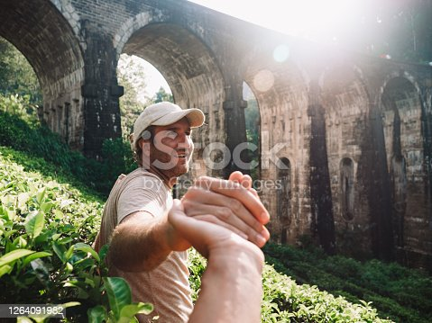 Two travelers holding hands man leading the way to famous sight in Ella, Sri Lanka.\nPeople travel sharing, pov woman following man leading the way