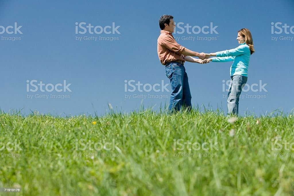 Couple holding hands on field royalty-free stock photo