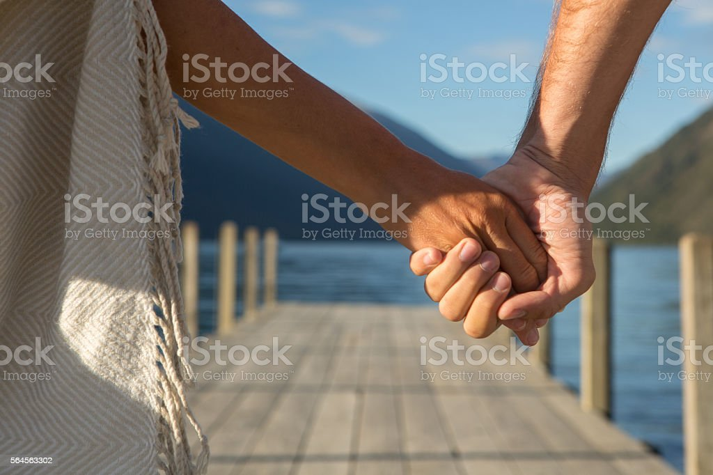 Couple holding hands on lake pier stock photo