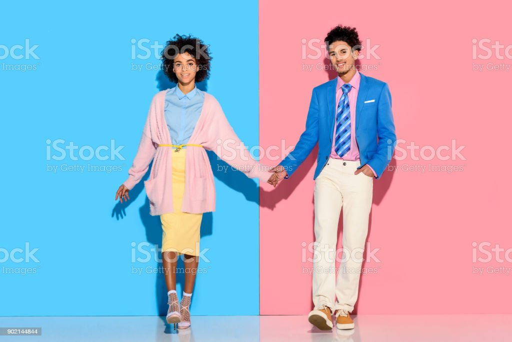 couple holding hands on pink and blue background happey couple holding hands on pink and blue background Adult Stock Photo