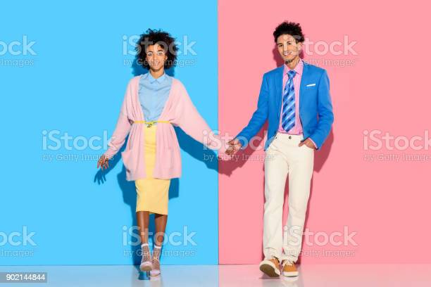 Couple Holding Hands On Pink And Blue Background Stock Photo - Download Image Now