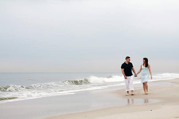 Pareja sosteniendo las manos en la playa. - foto de stock