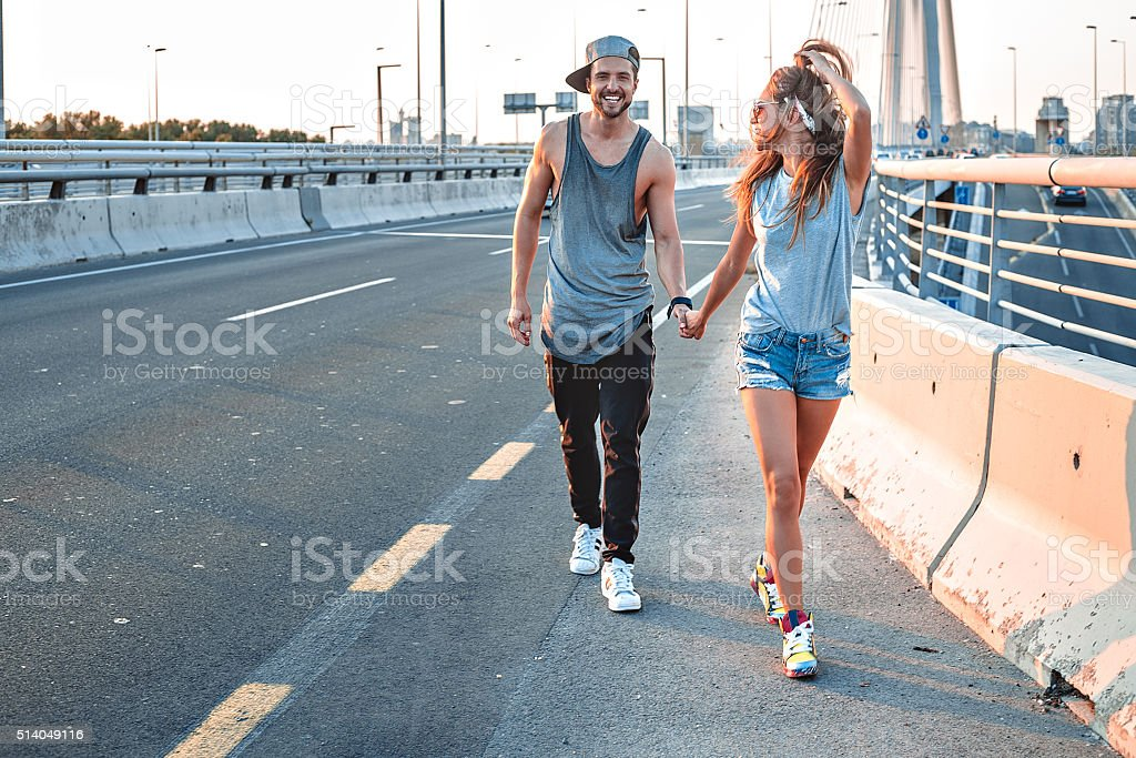 Couple holding hands on the street stock photo
