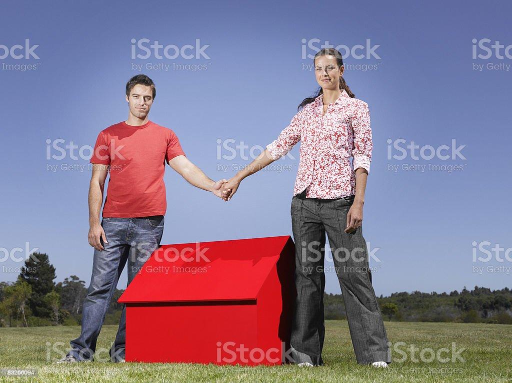 Coppia tenendo le mani sulla piccola Casa modello foto stock royalty-free