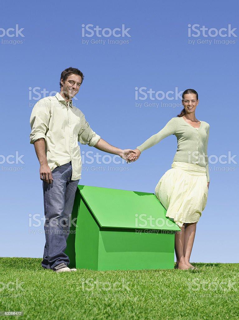 Paar Hände halten über kleine model house – Foto