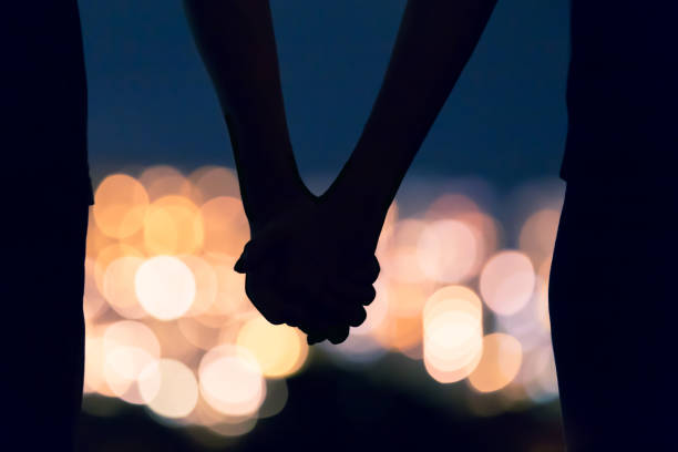 Couple holding hands Couple holding hands against city night lights. love at first sight stock pictures, royalty-free photos & images