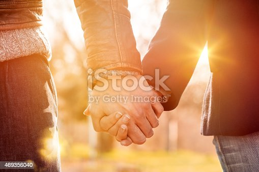 Closeup of loving couple holding hands while walking at sunset