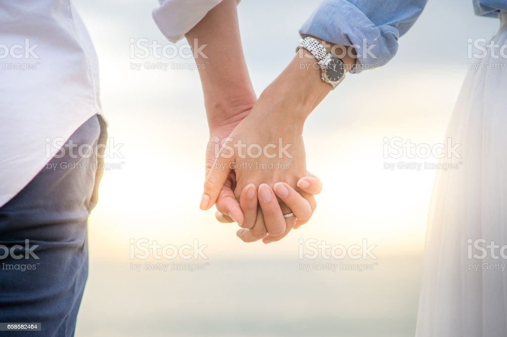Couple holding hands stock photo