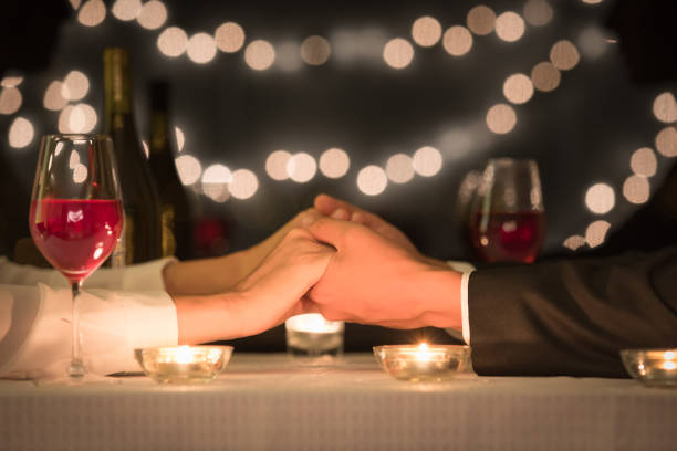 couple holding hands - dinner date stock photos and pictures