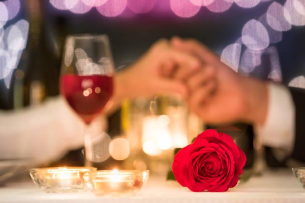 pareja sosteniendo las manos - cena romantica fotografías e imágenes de stock