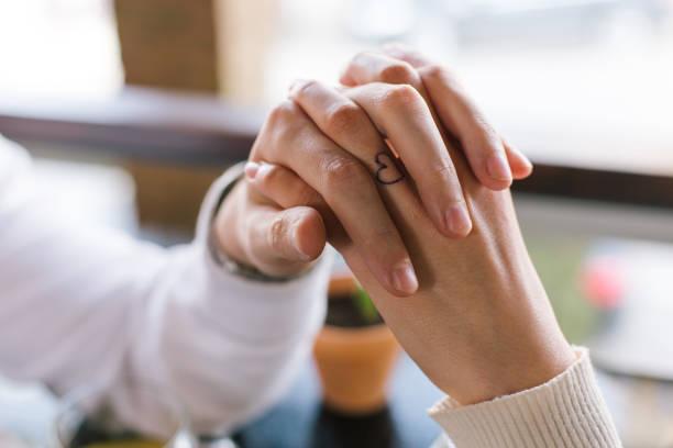 paar hände halten - ehepaar tattoos stock-fotos und bilder