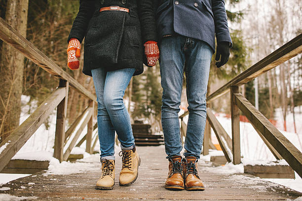 Couple holding hands standing in a winter forest straight stock photo