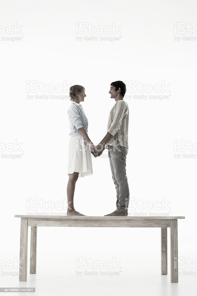 Couple holding hands standing on wooden table against white background royalty free stockfoto